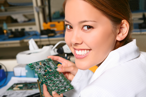 Contract worker inspecting circuit boards for quality